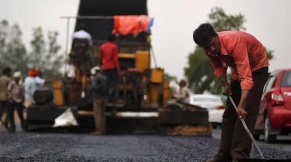 สภาพของคนงานที่กำลังการสร้างถนนที่แปลงถนนลูกรังให้เป็นลาดยาง